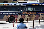 A bus with floor laminate advertising on the side is traveling with passengers on a street in Penang, Malaysia.