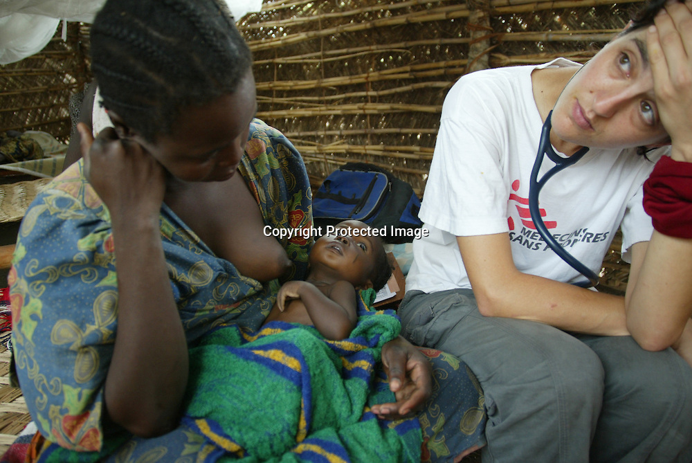 An tired MSF doctor sits next to a breastfeeding patient in CAR. In 2005, fighting broke out between government troops and various rebel groups in the northwest of the Central African Republic (CAR). More than 100,000 people have been forced to flee their homes in search of safety.