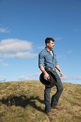 handsome cowboy on a grassy hillside