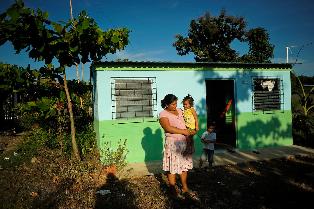 Jaqueline Esperanza Polanco, 27, poses for a portrait in front her home in the El Caoba housing complex with her daughter Darli, 2, and son, Geovanni, 4, in La Libertad, El Salvador. With support from the international ngo, Plan UK, after her home was destroyed during a flood in 2008, Polanco built her new home in El Caoba, where she lives with her children and raises corn and beans for a living.