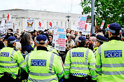 Police form a cordon as anti-fascists gather to protest against a march held by the English Defence League. Walthamstow London May 2015