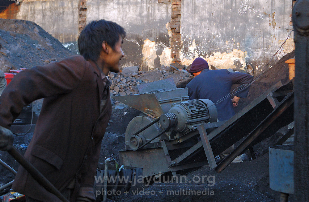 China, Beijing, Ping Fang Xiang, 2008. This coal brick stamping machine in Ping Fang Xiang can turn out hundreds of bricks per hour, provided it is fed by hand. Workers stand by to load three-wheel carts for neighborhood delivery.
