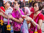 "19 FEBRUARY 2015 - BANGKOK, THAILAND:  Women pray on Chinese New Year at Wat Mangkon Kamalawat in Bangkok. 2015 is the Year of Goat in the Chinese zodiac. The Goat is the eighth sign in Chinese astrology and ""8"" is considered to be a lucky number. It symbolizes wisdom, fortune and prosperity. Ethnic Chinese make up nearly 15% of the Thai population. Chinese New Year (also called Tet or Lunar New Year) is widely celebrated in Thailand, especially in urban areas that have large Chinese populations.   PHOTO BY JACK KURTZ"
