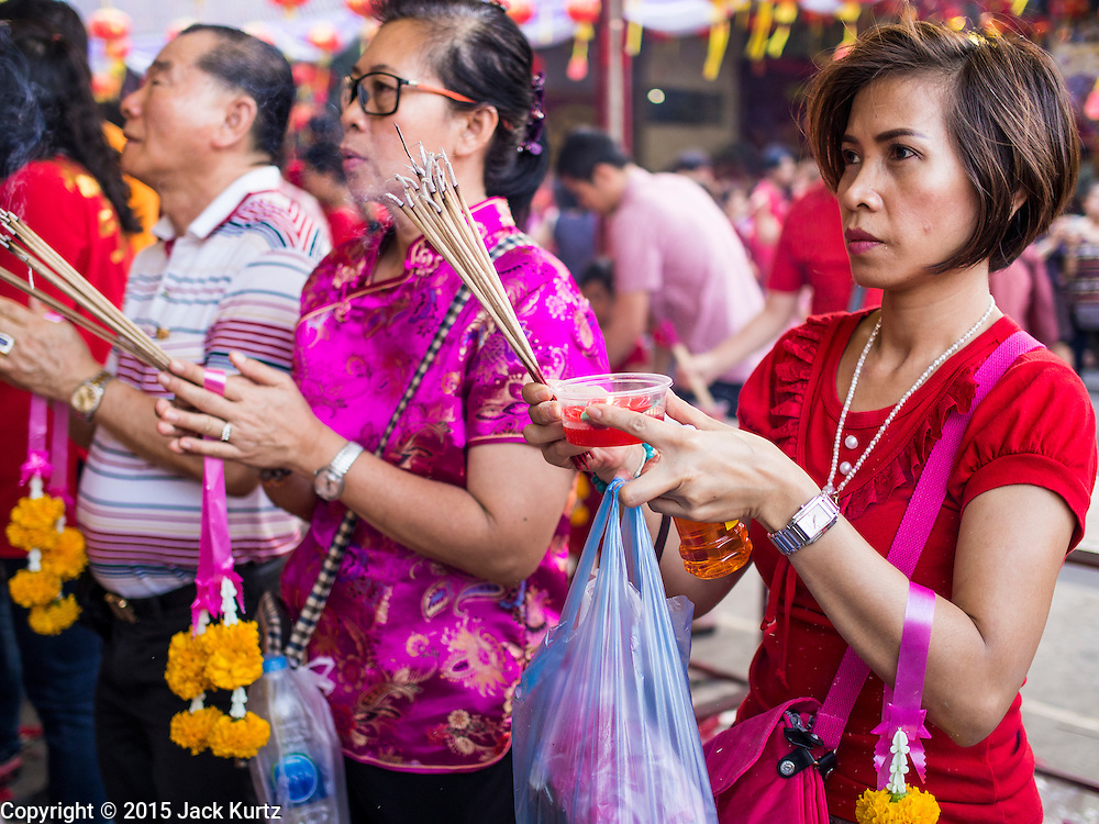 """19 FEBRUARY 2015 - BANGKOK, THAILAND:  Women pray on Chinese New Year at Wat Mangkon Kamalawat in Bangkok. 2015 is the Year of Goat in the Chinese zodiac. The Goat is the eighth sign in Chinese astrology and """"8"""" is considered to be a lucky number. It symbolizes wisdom, fortune and prosperity. Ethnic Chinese make up nearly 15% of the Thai population. Chinese New Year (also called Tet or Lunar New Year) is widely celebrated in Thailand, especially in urban areas that have large Chinese populations.   PHOTO BY JACK KURTZ"""