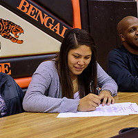 040315  Adron Gardner/Independent<br /> <br /> Gallup Bengal Cheyenne Livingston, center, signs a letter of intent to Haskell Indian Nations University in Kansas with her mother Shirlene Livingston, left, and varsity girls basketball coach Kamau Turner at Gallup High School Friday.
