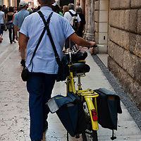 A postman and his bike in Verona.Verona is a city in Veneton, Northern Italy home to approx. 265,000 inhabitants and one of the seven provincial capitals of the region. Verona has Roman origins and  derived importance from being at the intersection of many roads. It is world famous for the Arena and its Opera....***Agreed Fee's Apply To All Image Use***.Marco Secchi /Xianpix. tel +44 (0) 207 1939846. e-mail ms@msecchi.com .www.marcosecchi.com
