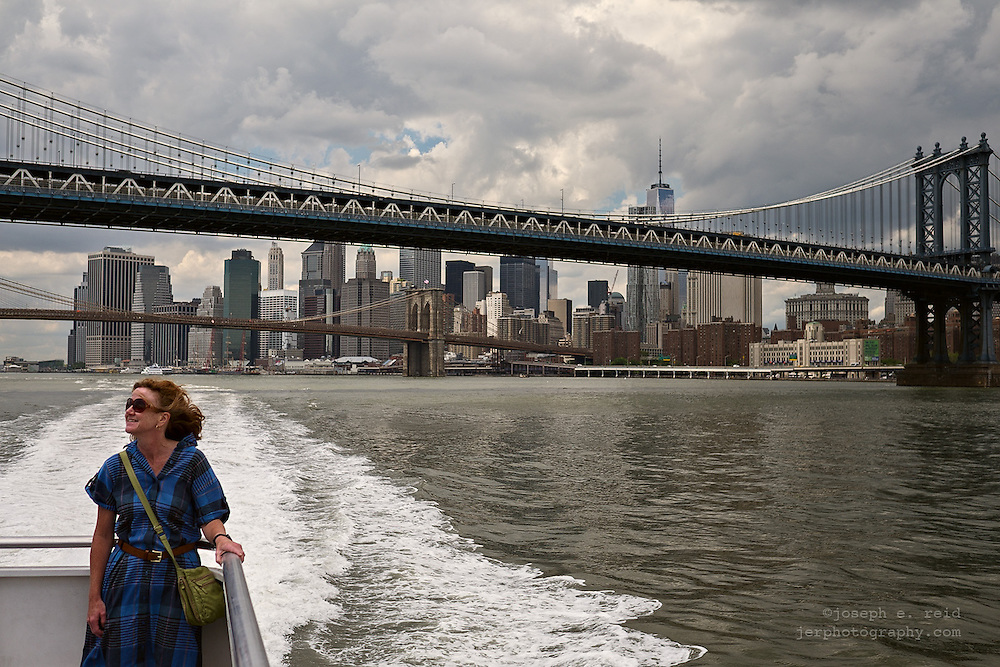 Smiling woman on ferry passing Brooklyn and Manhattan Bridges, New York, NY, US