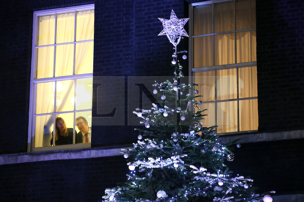 © Licensed to London News Pictures. 10/12/2015. London, UK. Downing street staff look from the window of 10 Downing Street as British Prime Minister DAVID CAMERON is joined by Points of Light award winners as he unveils this year's Downing Street Christmas tree. Photo credit: Peter Macdiarmid/LNP