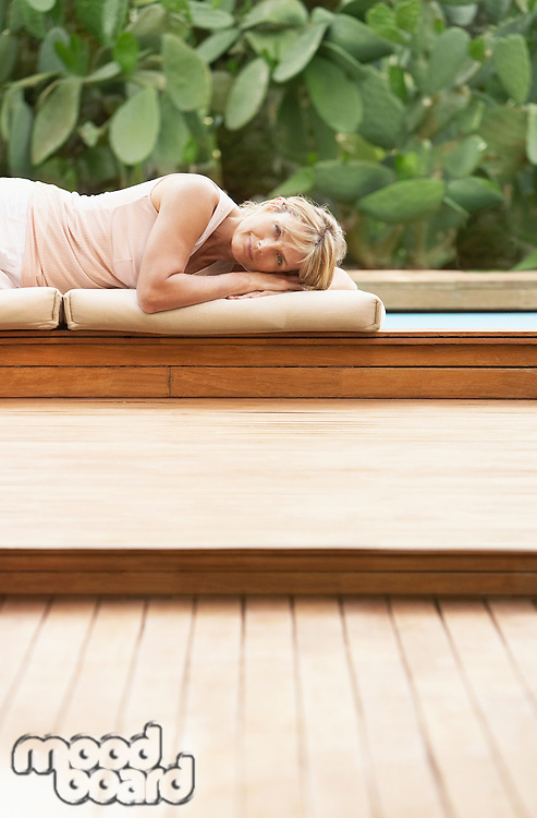 Middle-aged woman lying on cushions by pool portrait