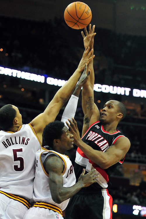 Feb. 5, 2011; Cleveland, OH, USA; Portland Trail Blazers forward Dante Cunningham (33) shoots over Cleveland Cavaliers center Ryan Hollins (5) and guard Christian Eyenga (8) during the first quarter at Quicken Loans Arena. Mandatory Credit: Jason Miller-US PRESSWIRE