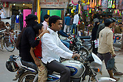 Young Indian Muslim family ride motorcycle in street scene in city of Varanasi, Benares, Northern India