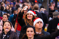 "London, December 23rd 2014. Dubbed by retailers as the ""Golden Hour"" thousands of shoppers use their lunch hour to do some last minute Christmas shopping in London's West End. PICTURED: A woman takes a selfie as she and thousands of others make their way along Oxford Street."