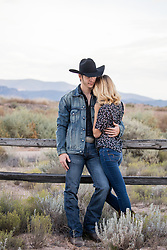 hot cowboy with a beautiful girl leaning against a fence