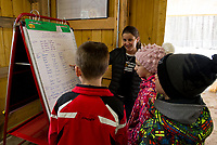 Principal Danielle Bolduc goes over the recordings of sap collected so far in 2019 with Brent Howard, Jacoby Drouin and Alison Nutter at their new sap house at Gilford Elementary School.  (Karen Bobotas/for the Laconia Daily Sun)