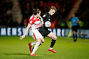 John Marquis of Doncaster Rovers  and Barnsley defender Liam Lindsay (6)  contest a loose ball  during the EFL Sky Bet League 1 match between Doncaster Rovers and Barnsley at the Keepmoat Stadium, Doncaster, England on 15 March 2019.