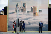 Tourists await a bus beneath a property developer's billboard showing a large aerial image of London skyscrapers in low cloud.