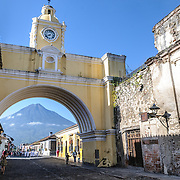 Under the clock tower of the Santa Catalina arch over the street in Antigua, Guatemala, one can see the Volcán de Agua in the distance.