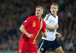 CARDIFF, WALES - Friday, October 12, 2012: Wales' Steve Morison in action against Scotland's Christophe Berra during the Brazil 2014 FIFA World Cup Qualifying Group A match at the Cardiff City Stadium. (Pic by David Rawcliffe/Propaganda)