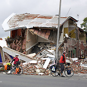 Cyclists stop to review an earthquake damaged building in Christchurch. after a Powerful earth quake ripped through Christchurch, New Zealand on Tuesday lunch time killing at least 65 people as it brought down buildings, buckled roads and damaged houses, churches and the Cities Cathedral. 23rd February 2011.  Photo Tim Clayton