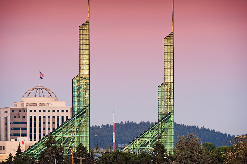 The Oregon State Office Building (left) and twin glass spire towers of the Oregon Convention Center dominate the urban skyline in the Lloyd District neighborhood of Portland, Oregon. The State Office Building was designed by the architecture firm of GBD Architects and the Convention Center was designed by Zimmer Gunsul Frasca Architects (ZGF).  Mount Tabor, an extinct volcano within the city limits, is visible in the background.