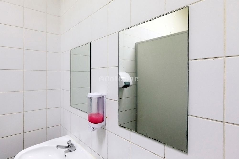mirror sink and soap dispenser in a public badroom
