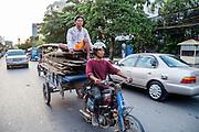 Twee mannen vervoeren hout op een aanhanger achter een motor.