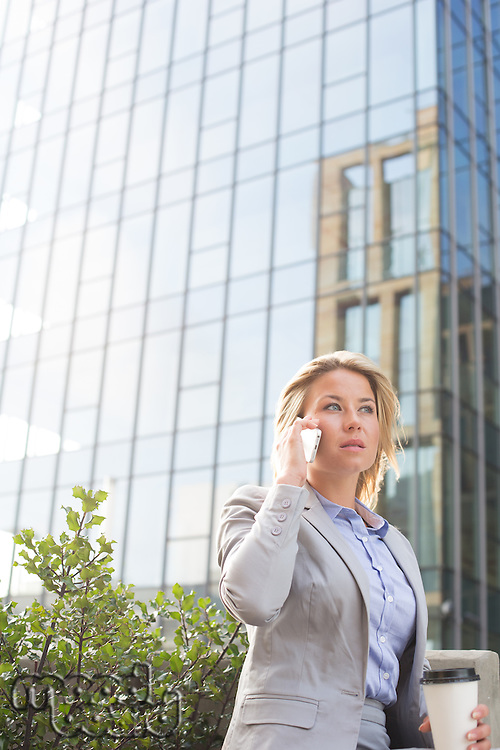 Businesswoman using mobile phone outside office building