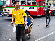 17 MAY 2013 - BANGKOK, THAILAND:  A porter pulls a basket down Chakphet Road in front of the flower market in Bangkok. The Bangkok Flower Market (Pak Klong Talad) is the biggest wholesale and retail fresh flower market in Bangkok. It is also one of the largest fresh fruit and produce markets in the city. The market is located in the old part of the city, south of Wat Po (Temple of the Reclining Buddha) and the Grand Palace.   PHOTO BY JACK KURTZ