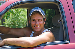 man smiling while looking out the window of a truck