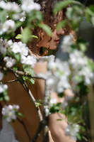 Artistic sensual portrait of a beautiful nude young woman behind white flowers of apple blossom outdoors in spring