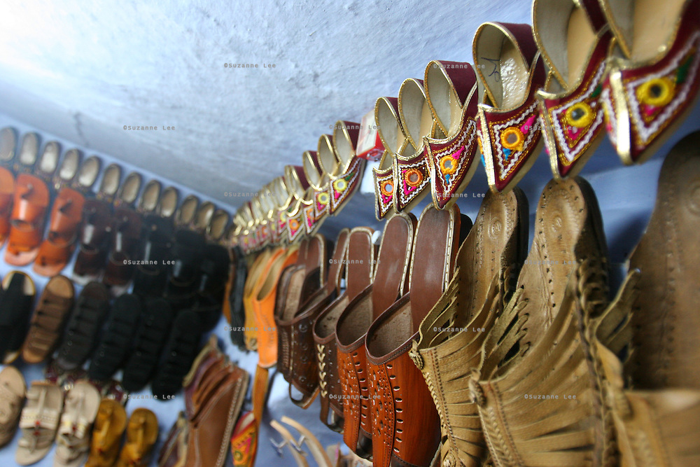 Details of the racks of a jootie shoe merchant in Pushkar, Rajasthan, India. Every year in November thousands of Rajasthani tribal people converge in the picturesque town of Pushkar, which is also a major site for Hindu pilgrims. They come to buy and sell camels (over 50,000) and other cattle and bathe at the Pushkar lake (considered sacred by Hindus). They come for the entertaining camel races and local circuses, and to browse the local markets for camel saddles, textiles, glass bangles and silver jewelry..Photo by Suzanne Lee