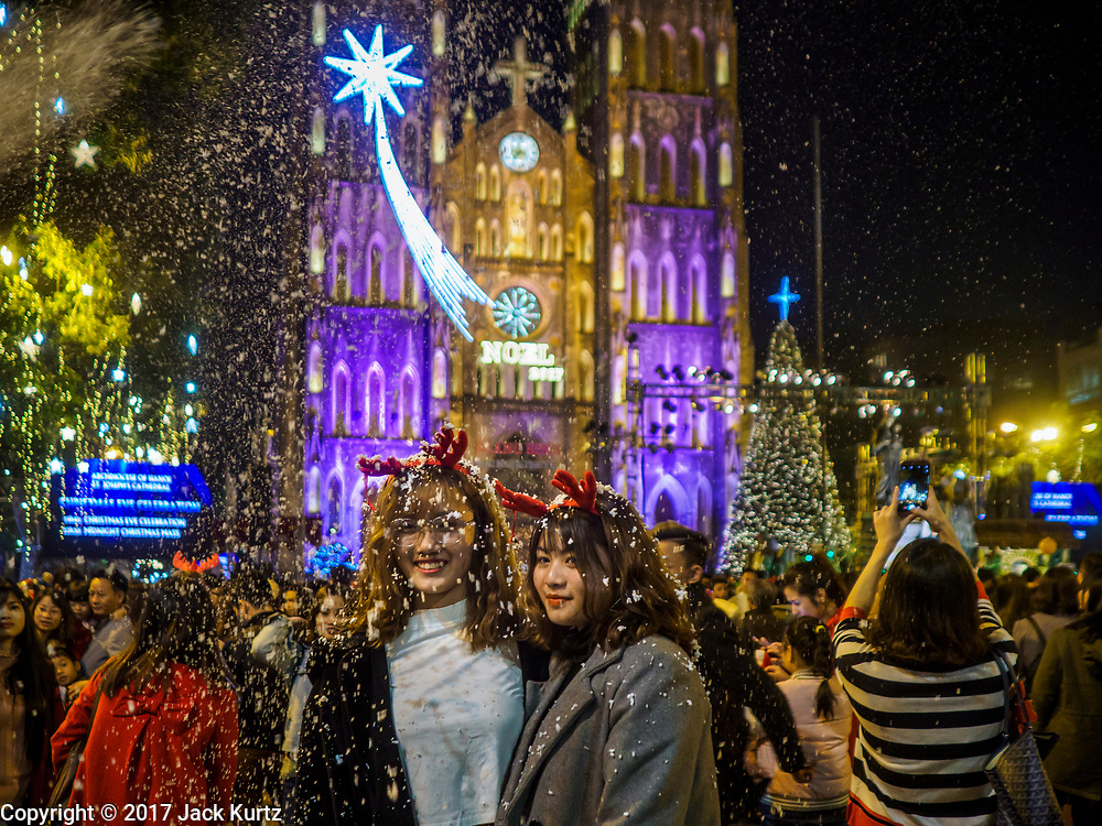 24 DECEMBER 2017 - HANOI, VIETNAM:  Vietnamese women walk through a blizzard of artificial snow, shot out of a can, during the Christmas Eve celebration in front of St. Joseph's Cathedral in Hanoi. The commercial and gift giving aspect of Christmas is widely celebrated in Vietnam and Vietnam's 5+ million Catholics celebrate the religious aspects of Christmas.    PHOTO BY JACK KURTZ