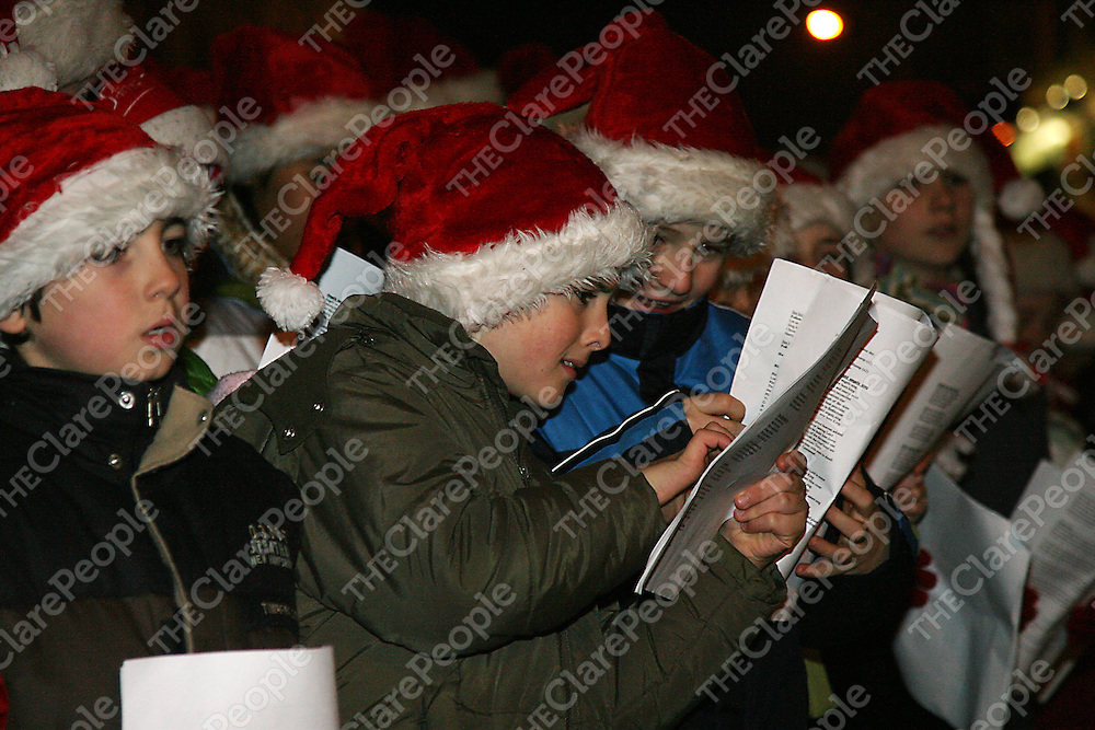 Members of the choir check thier lyrics at the annual switching on of the Christmas lights in Ennis on Thursday evening.<br />