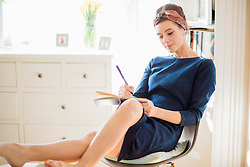 Woman Sitting on Chair Writing on Notebook