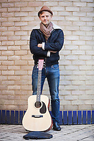 Portrait of happy young man with guitar standing against brick wall