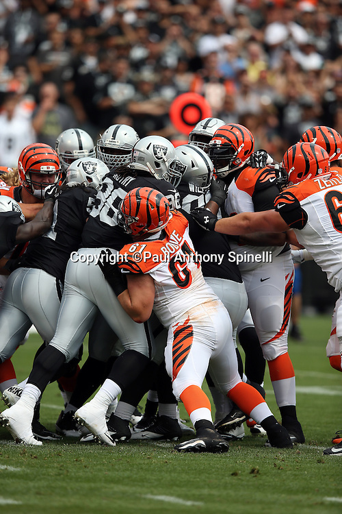Cincinnati Bengals center Russell Bodine (61) tries to push a pile of defenders as the Oakland Raiders defense makes a goal line stand on third down during the 2015 NFL week 1 regular season football game against the Oakland Raiders on Sunday, Sept. 13, 2015 in Oakland, Calif. The Bengals won the game 33-13. (©Paul Anthony Spinelli)