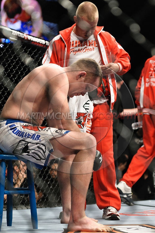 """LAS VEGAS, NEVADA. JULY 11, 2009: TJ Grant (seated) is visibly dejected after losing his fight at """"UFC 100: Making History"""" inside the Mandalay Bay Events Center in Las Vegas, Nevada."""