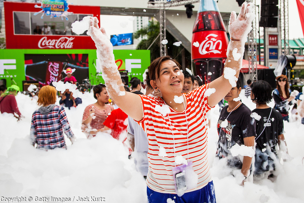 14 APRIL 2013 - BANGKOK, THAILAND:  A woman plays in the foam pool at Central World on April 14, 2013 in Bangkok, Thailand. The Songkran festival is celebrated in Thailand as the traditional New Year's Day from 13 to 15 April. The throwing of water originated as a way to pay respect to people and is meant as a symbol of washing all of the bad away. PHOTO BY JACK KURTZ