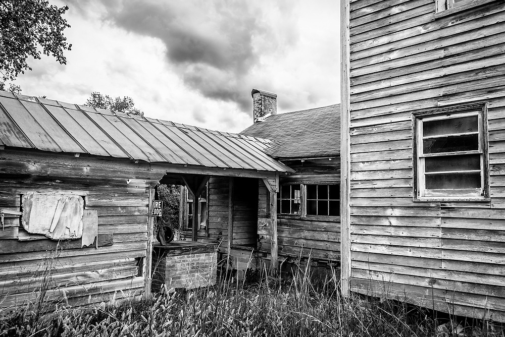 The soft lines and flowing organic shapes of dramatic rain clouds contrast with the hard lines and shapes of this abandoned old house.  The image finished with an Exposure 7 filter emulating Agfa APX 100 black & white film.