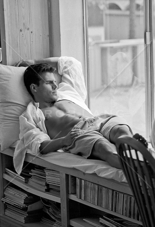 good looking man with an open shirt relaxing at home in a window seat