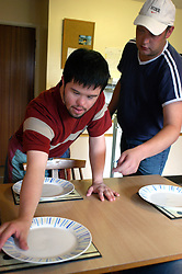 Man with learning disability setting table for meal in sheltered housing scheme with help from support worker; UK