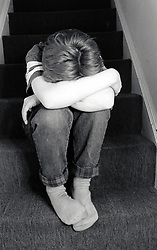 Boy sulking on the stairs. Posed by model UK 1989