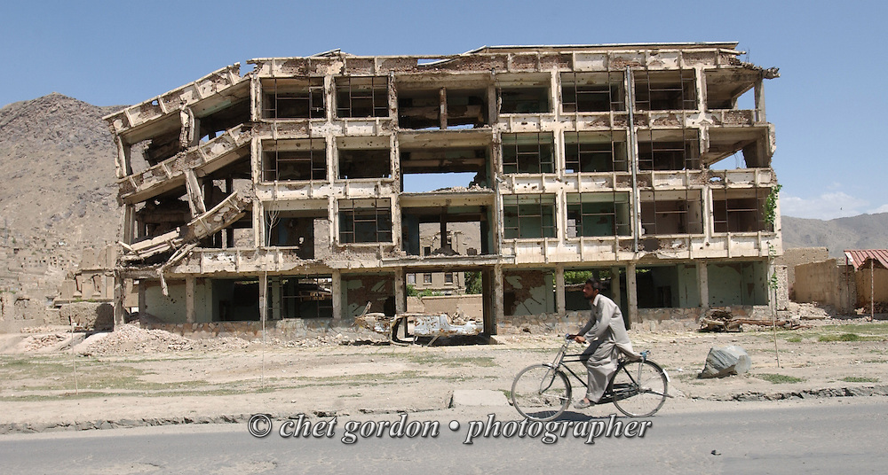 A bicyclist passes a destroyed building in Kabul, Afghanistan on Sunday, May 26, 2002.