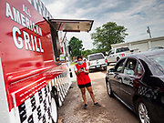 "26 JUNE 2020 - DES MOINES, IOWA: NADINE GARCIA, a worker at the American Grill trailer, waits for a customer's food at Fair Food Friday in Des Moines. The 2020 Iowa State Fair, like many state fairs in the Midwest, has been cancelled this year because of the COVID-19 (Coronavirus) pandemic. The cancellation of the fair left many small vendors stranded with no income. Some of the fair food vendors in Iowa started ""Fair Food Fridays"" on a property a few miles south of the State Fairgrounds. People drive up and don't leave their cars while vendors bring them the usual midway fare; corndogs, fried tenderloin sandwiches, turkey legs, deep fried Oreos, lemonaide and smoothies. Fair Food Friday has been very successful. The vendors serve 450-500 people per Friday and during the lunch rush people wait in line in their cars 30 - 45 minutes to place an order.      PHOTO BY JACK KURTZ"