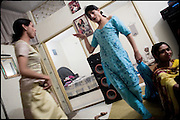 "Nadia (on the right), 21 years old, Kastouri (in the middle), 16 years old, and Chabbo (on the left), 32 years old, all transvestites at their  common apartment. Evening in Lahore, Pakistan on Monday, December 01 2008.....""Not men nor women"". Just Hijira, Kusra. Painted lips, Kajal surrounding their eyes and colourful veils..Pakistan is today considered a strongly, foundamentalist as well, islamic country. But under its reputation, above all over the talebans' continuos advancing, stirs a completely extraneous world, a multiethnic mixed society. Transvestites make part of it, despite this would not be admitted by a strict law. Third gender, the Hijira are born as men (often ermaphrodites) or with an ambiguous genital situation, and they have their testicles and penis removed through a - often brutal - surgical operation. The peculiarity is that this operation does not contemplate the reconstruction of a female organ. This is the reason why they are not considered as men nor women, just Hijira. They are often discriminated, persecuted  and taxed with being men prostitutes in the muslim areas. The members of this chast perform dances during celebrations, especially during weddings, since it is anciently believed that an EUNUCO's dance and kiss in the wedding day brings good luck to the couple's fertility...To protect the identities of the recorded subjects names and specific .places are fictionals."