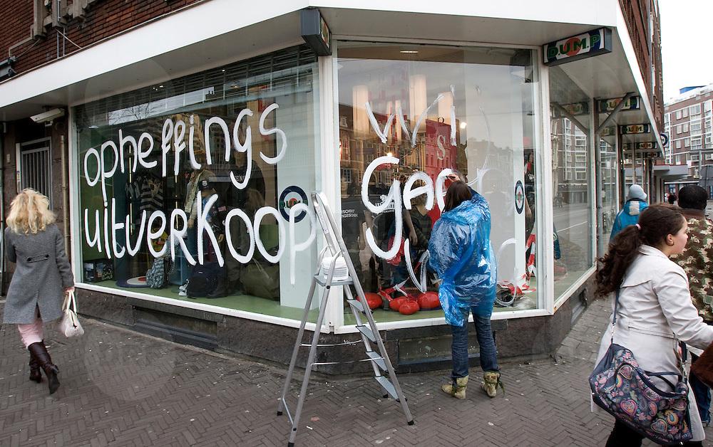 Nederland, Den Haag,18 februari 2009 20090218 Foto: David Rozing .Kredietcrisis, recessie, sluiting winkel, opheffingsverkoop, werknemer verrft verkoopleuzen op de etalage ramen: opheffingsverkoop, wij gaan weg..Foto: David Rozing