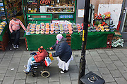 A disabled woman pushed by her carer pass-by a fresh fruit stall in a south London street.