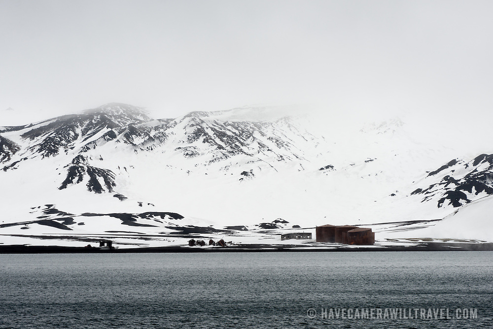 Ruins of buildings and oil tanks at the former whaling station at Whalers Bay on Deception Island. Deception Island, in the South Shetland Islands, is a caldera of a volcano and is comprised of volcanic rock.