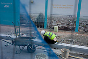 A dystopian landscape of construction materials and an inspirational view above the city - seen through a wire and netting street fence. Lettering on the hoarding tells us the scene below is inspirational, a capital from a new perspective. But the mess of aggregates and soil, tools and rubble tell a different story: an incongruous landscape of an idealised city and the reality of unfinished work.