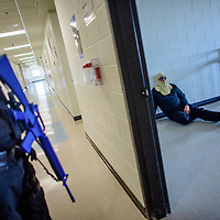 """McKinley County Sheriff deputy Garylle James, left, guards a mock crimes scene as Jerijah Triplett, District Fire Chief for Ft Wingate Fire Department, whole played the part of """"active shooter' takes a rest during an Active Shooter training exercise at Wingate High School Friday."""